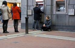 在ATM机器的Begger 图库摄影