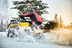 在ATV的冬天种族在雪在森林里 免版税库存照片