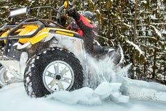 在ATV的冬天种族在雪在森林里 免版税库存图片