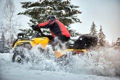 在ATV的冬天种族在雪在森林里 库存照片