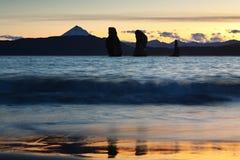 在Avachinskaya海湾的三个兄弟岩石在日落 俄罗斯,远东,堪察加 免版税图库摄影