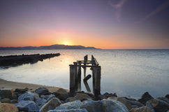 在awesoome美好的日落期间的老打破的码头 充满活力的颜色 库存图片