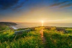 在Azkorri附近的长凳靠岸与多暴风雨的天气在日落 库存图片
