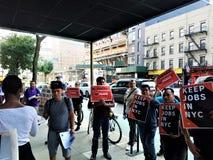 在B&H照片商店之外的人在有标志的曼哈顿在NYC在手上保留工作抗议有联合支持 免版税库存照片