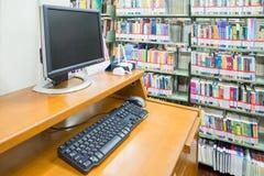 在backgro的计算机在有许多书的一个图书馆里和架子 库存图片