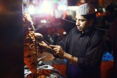 年轻在Bahadurabad的人smaking的shawarma 免版税库存图片