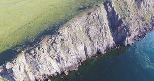 在Baikal湖的岩石海岸的圆飞行 有太阳的反射在贝加尔湖中水域的 股票视频