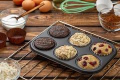 在bakeware或松饼平底锅的不同的松饼在broun木背景 基本的松饼食谱 早餐或des的自创松饼 图库摄影