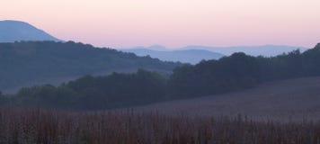 在Bakhchisaray山的黎明:山对角倾斜,轻的阴霾创造音调的透视,一个紫色淡紫色领域 库存照片