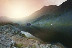 在Balea湖的日落 在美好的地点的小屋客舱 库存照片