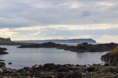 在Ballintoy港口的海滩北爱尔兰北部安特里姆海岸的有它的石被修造的船库的在一天在春天 库存图片