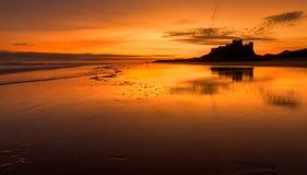 在Bamburgh海滩的金黄日出 库存图片