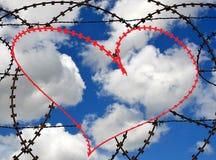 在barbwire的红色心脏在天空背景 免版税库存图片