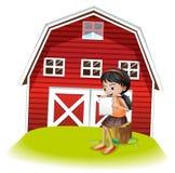 在barnhouse前面的女孩读书 图库摄影
