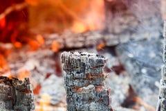 在BBQ格栅坑与火焰背景纹理,特写镜头的发光的热的木炭 免版税库存图片