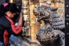在Bhaktapur Durbar广场,尼泊尔的狮子古铜色顶头雕象 库存图片