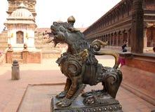 在Bhaktpur Darbur广场的一个美丽的古铜色狮子雕象 库存照片