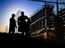 在Bl的一个建筑工地现出轮廓看图纸的工程师 免版税库存图片