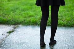 在blck贴身衬衣和裙子的女性腿在多雨湿公园道路和草减速火箭的颜色 免版税图库摄影