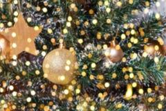 在blured树特写镜头的圣诞节金黄装饰品 免版税库存图片