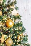 在blured树特写镜头的圣诞节金黄装饰品 图库摄影
