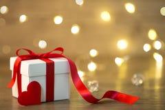 在boke背景的礼物盒 红色丝带 心脏 免版税库存图片