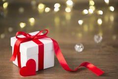在boke背景的礼物盒 红色丝带 心脏 免版税库存照片