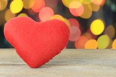 在bokeh背景的一个木地板安置的红色心脏 免版税库存照片