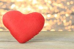 在bokeh背景的一个木地板安置的红色心脏 库存图片