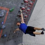 在bouldering的墙壁上的攀岩运动员执行的旗杆 库存照片