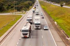 在BR-374高速公路的车有车灯的在服从新的巴西运输法律的白天期间 免版税库存照片