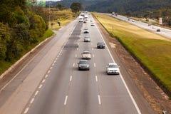 在BR-374高速公路的车有车灯的在服从新的巴西运输法律的白天期间 免版税库存图片