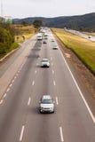 在BR-374高速公路的车有车灯的在服从新的巴西运输法律的白天期间 库存照片