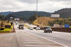 在BR-374高速公路的车有车灯的在服从新的巴西运输法律的白天期间 库存图片