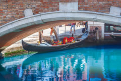 在brige下的停车处长平底船在其中一条威尼斯,意大利运河中  免版税图库摄影