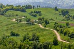 在Bucovina农村,罗马尼亚的美丽的弯曲的路 免版税库存图片
