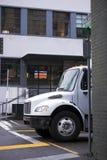 在buildi围拢的城市街道上的白色中间半大小卡车 免版税图库摄影
