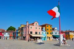 在Burano海岛广场正方形上的大意大利旗子飞行 库存图片