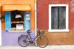 在Burano街道海岛上的五颜六色的房子有一辆自行车的在窗口附近,威尼斯 免版税库存图片