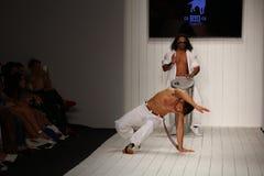 在CA-RIO-CA时装表演期间,舞蹈家执行在跑道的capoeira 免版税库存图片