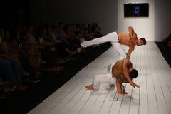 在CA-RIO-CA时装表演期间,舞蹈家执行在跑道的capoeira 免版税图库摄影