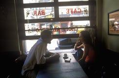 在Cafï ¿ ½夫妇和热奶咖啡的男人和妇女饮用的咖啡,她在布宜诺斯艾利斯,阿根廷抽香烟 库存照片