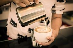在capuccino咖啡的Barista倾吐的牛奶 免版税库存图片