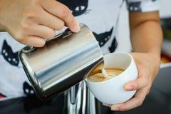 在capuccino咖啡的Barista倾吐的牛奶 免版税库存照片
