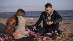 在casualwear的年轻家庭坐格子花呢披肩由海滨和有热的饮料在野餐 冷天,周末 股票录像