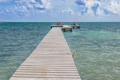 在Caye填缝隙工伯利兹加勒比的木码头船坞和海景 免版税图库摄影
