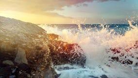 在Ccoastal石头的波浪断裂和轮到天际和日落的泡沫海里 免版税库存图片