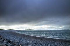 在Cemlyn海湾, Anglesey上的剧烈的天空在北部威尔士 库存图片