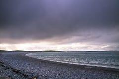 在Cemlyn海湾, Anglesey上的剧烈的天空在北部威尔士 免版税库存图片