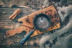 在cezve的咖啡在一张土气木桌上用香料、桂香和咖啡豆 艺术美丽的照相机注视看起来充分的魅力绿色关键字的嘴唇低做照片妇女的纵向紫色的方式 定调子 库存图片